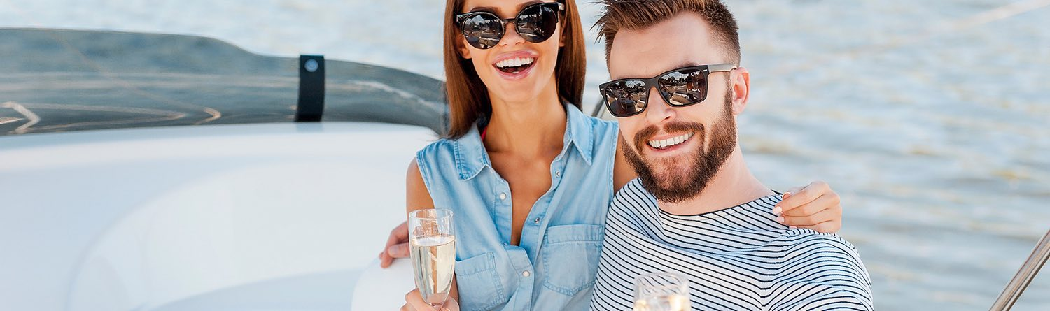 a man and woman smile for a picture while sitting on a boat drinking champagne