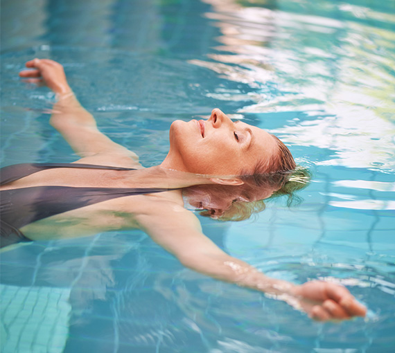 a woman floating in the pool with her arms stretched out