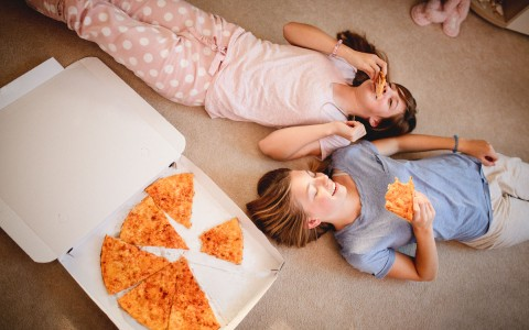 Two Teenagers Laying Down Eating Pizza
