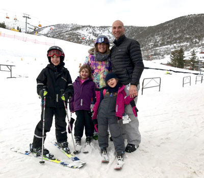 family in their ski gear standing together at the bottom of the mountain