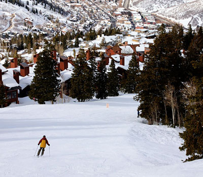 skier going down the mountain with Park City town in the background