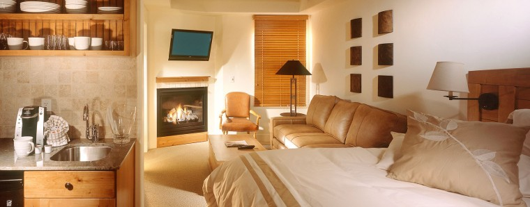 photo of suite with a fireplace, couch, and kitchen 6