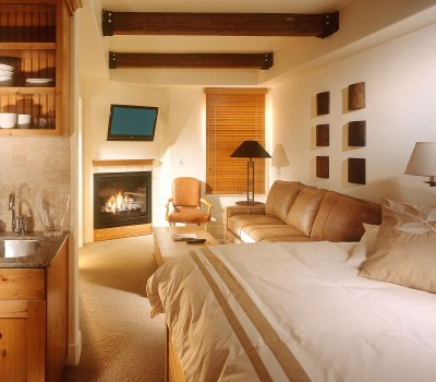 photo of suite with a fireplace, couch, and kitchen