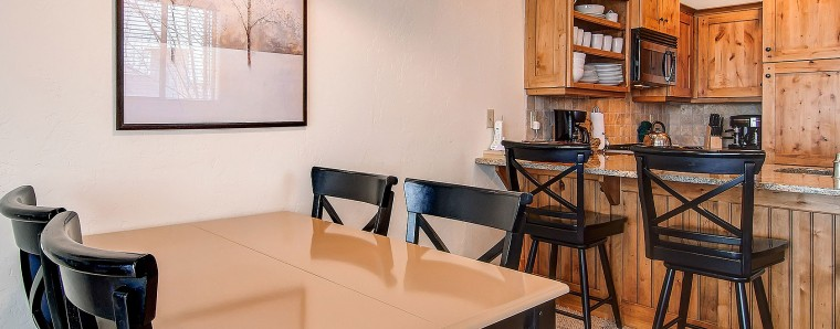 photo of townhome dining table and kitchen with bar stools