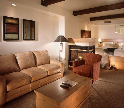 photo of a suite with a bed, fireplace and living room