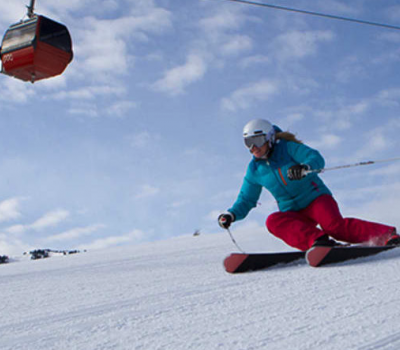 Image of skier carving the slopes at Newpark with a red gondola behind her