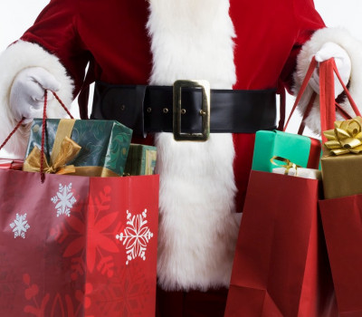 Shopper in Santa Claus Costume Holds Many Gift Wrapped Packages in Holiday Bags