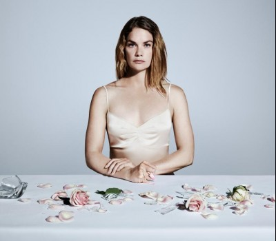 woman sitting at a table with flower pedals and broken glass