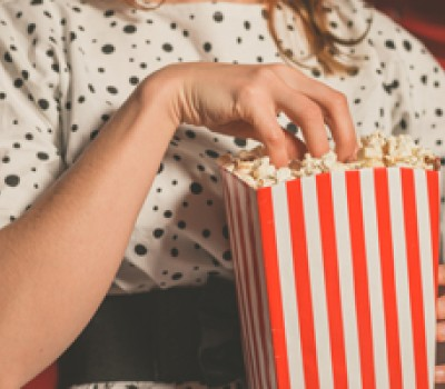 woman sitting in a movie with her hand in a popcorn bag