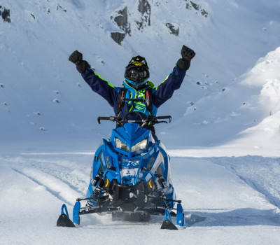 person with raised hands riding blue snowmobile