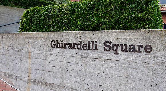Ghirardelli Square sign with bushes on top