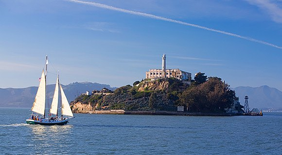 Stone Alcatraz Island with boat sailing by