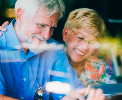 Older couple smiling while using a laptop