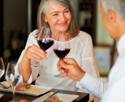 Old couple toasting with red wine