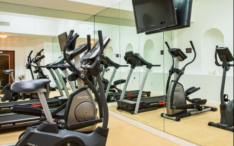 Fitness center with machinery, mirrors & TV