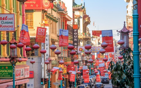 Chinatown street with Chinese signs & lanterns strung across