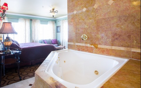 Big white tub next to king bed in room