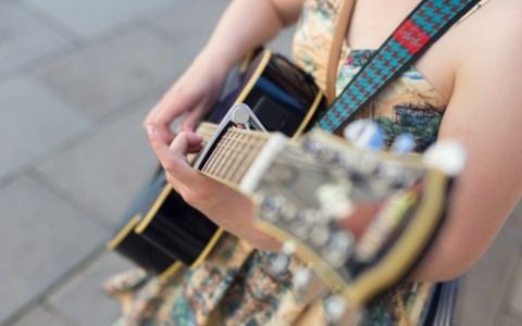 female street musician playing guitar