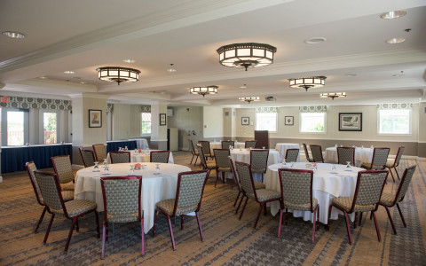 event room set up with round chairs draped with white table cloths for a meeting