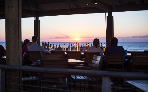 a view of the sunset over the ocean seen from behind the bar area at the beach bar