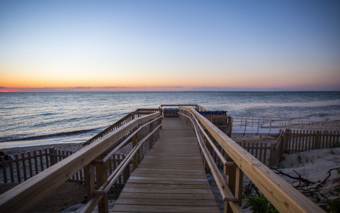 boardwalk leading towards the ocean water at sunset