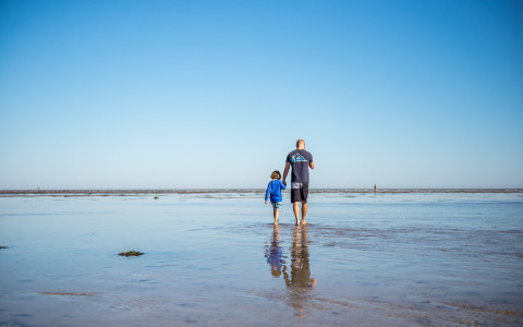 a father and child walking along the beach