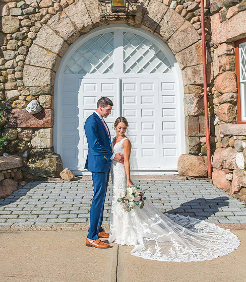 bride and groom posing in front of door