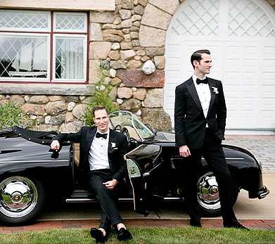 grooms posing in front of car