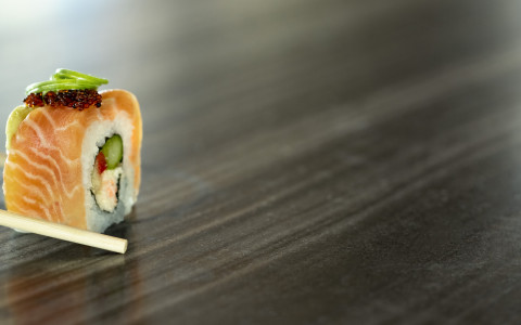 Up close of the Salmon Sushi Roll held with chopsticks