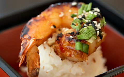 Grilled shrimp on top of rice with green onion garnish