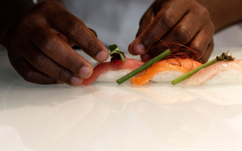 Close up of chef's hands plating raw sushi