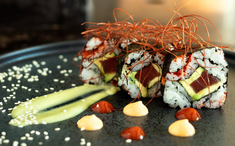 Sushi roll with sauce and herb garnish