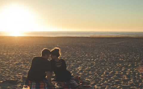 couple sitting beach sunset