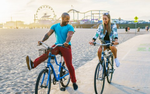 Couple bike riding by Pier