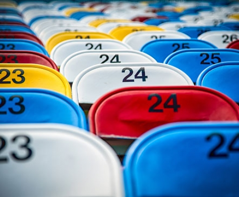 Close up of colorful chairs with numbers lined up on bleachers