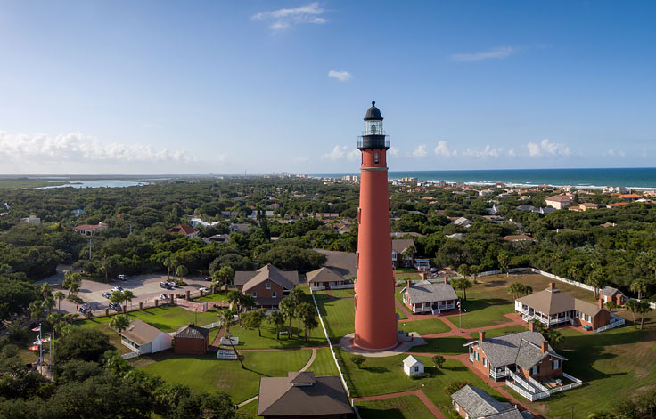 Aerial view of lighthouse surrounded by houses & greenery