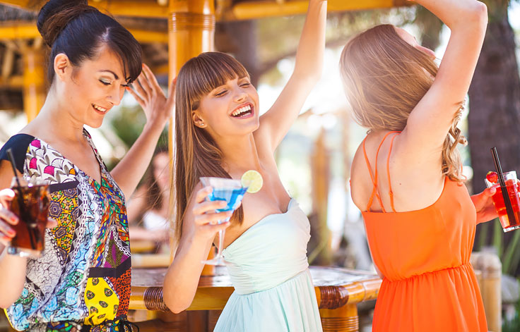 Women dancing outside with cocktails in hand