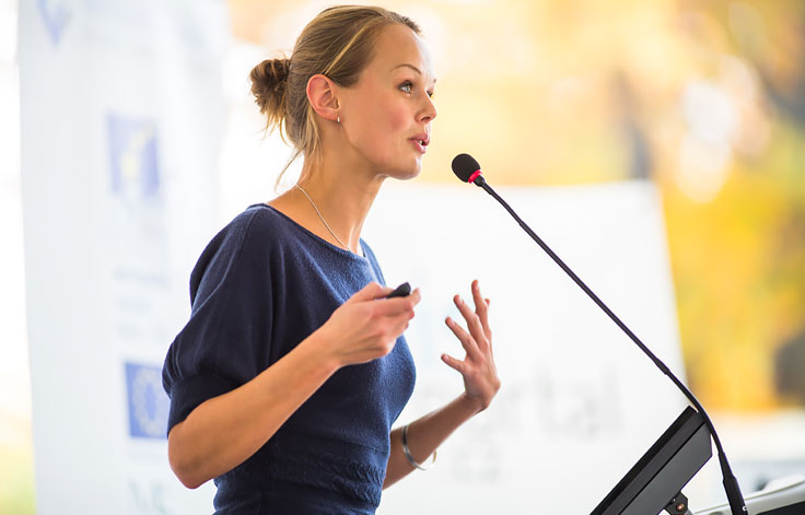 Woman talking into podium microphone with remote in hand