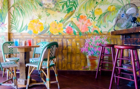 Dining space with whicker chairs, wooden tables, stools & tropical flowers painted on wall