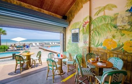 Dining area with tables & chairs exposed to the outdoors & with tropical plants painted on walls