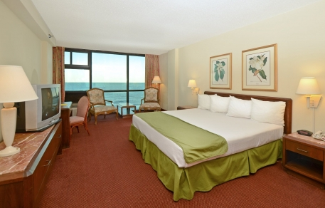Room with king bed, wooden nightstand, dresser, Tv & seating area next to balcony with ocean view