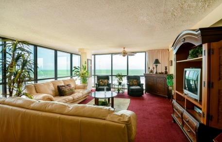 In room living space with leather sectional sofa, wooden furniture, Tv & large window panels exposing ocean view
