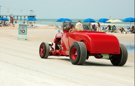 Red two passenger convertible riding along beach