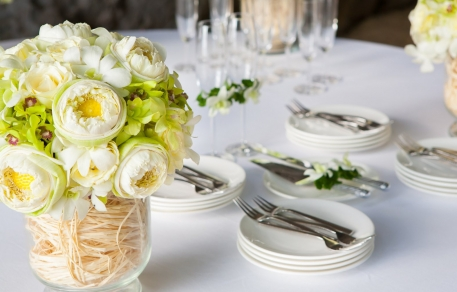 Table with white plates, silver forks, wine glasses & white flower centerpiece arrangement
