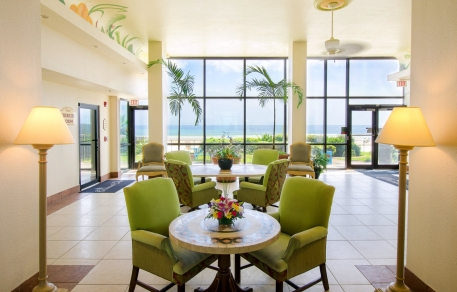 Lobby with circular tables, green sofa chairs & large window panels with ocean view