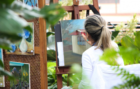 woman painting outside on easel