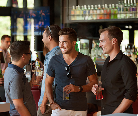 three men holding drinks and chatting at a bar