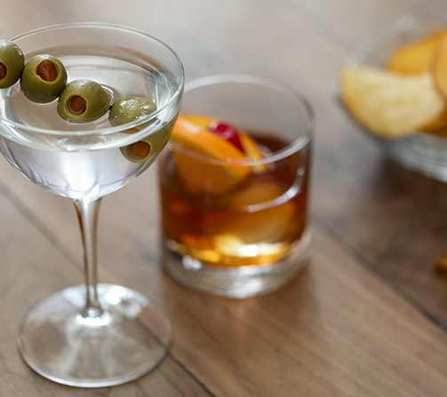 Martini with olives and a glass of scotch with orange slice