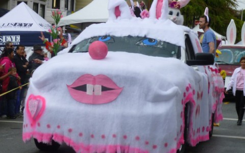 a car with a cover over it costumed as a pink and white bunny rabbit