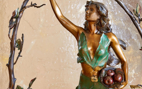 statue of woman holding apple
